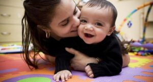 Hispanic woman with infant playing on mat